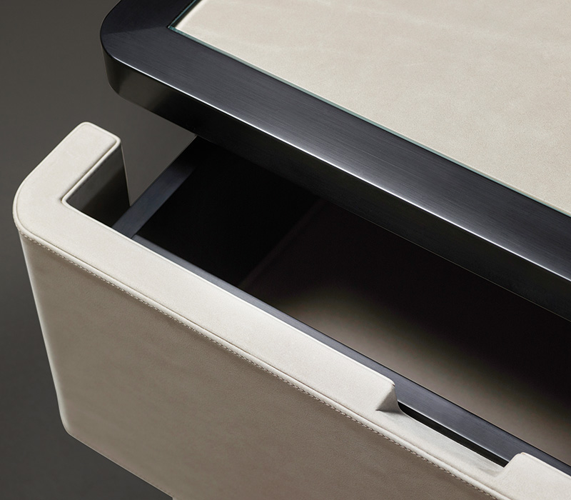 Drawer detail of Au Bout de la Nuit, a wooden bedside table with drawers, bronze base and top covered in leather with glass, from Promemoria's Amaranthine Tales collection | Promemoria