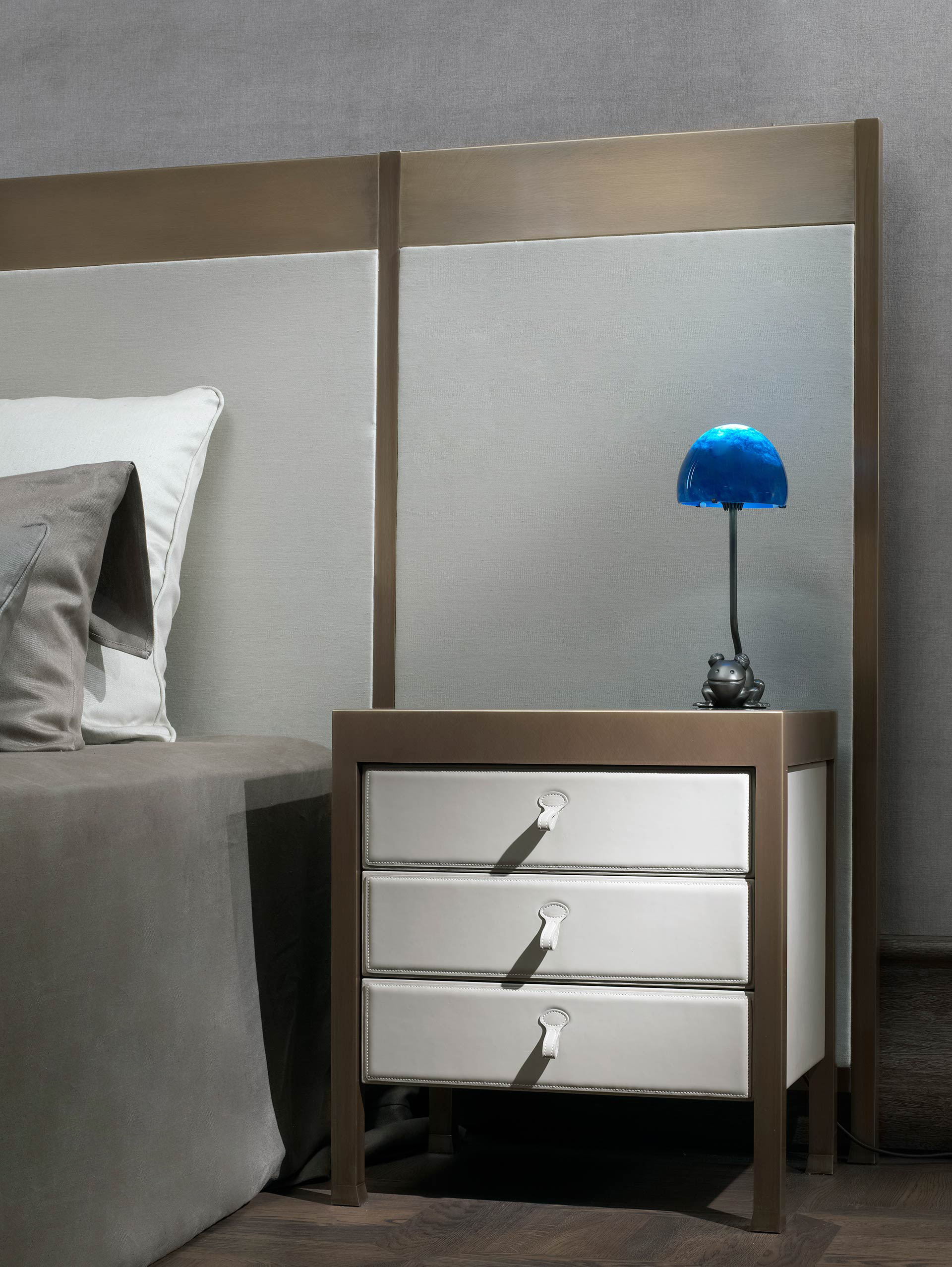 Gong is a bronze bedside table that can be covered in fabric or leather, from the Promemoria's catalogue | Promemoria