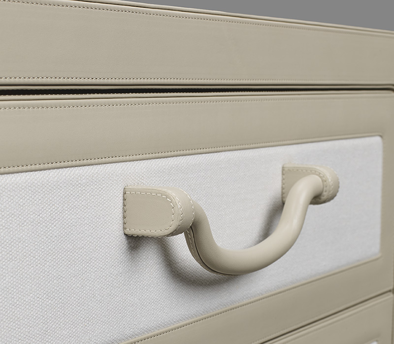 Handle detail of Future Voyager Atto II, a wooden chest of drawers covered in leather and fabric with handles and placemats in leather from Promemoria's catalogue | Promemoria