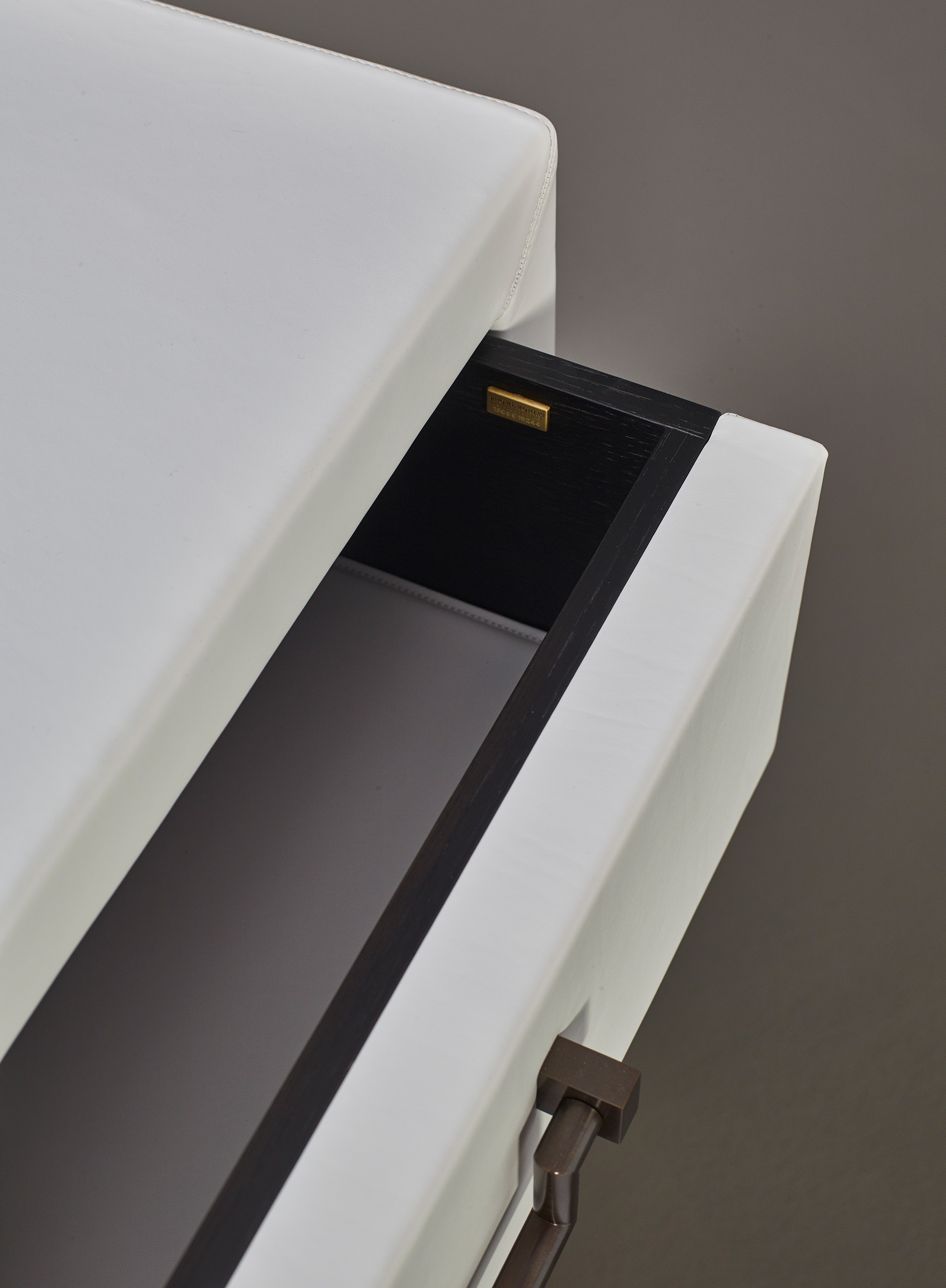 Drawer detail of Future, a wooden chest of drawers covered in leather or fabric with leather placemats and handles in leather or bronze, nickel and chrome from Promemoria's catalogue | Promemoria