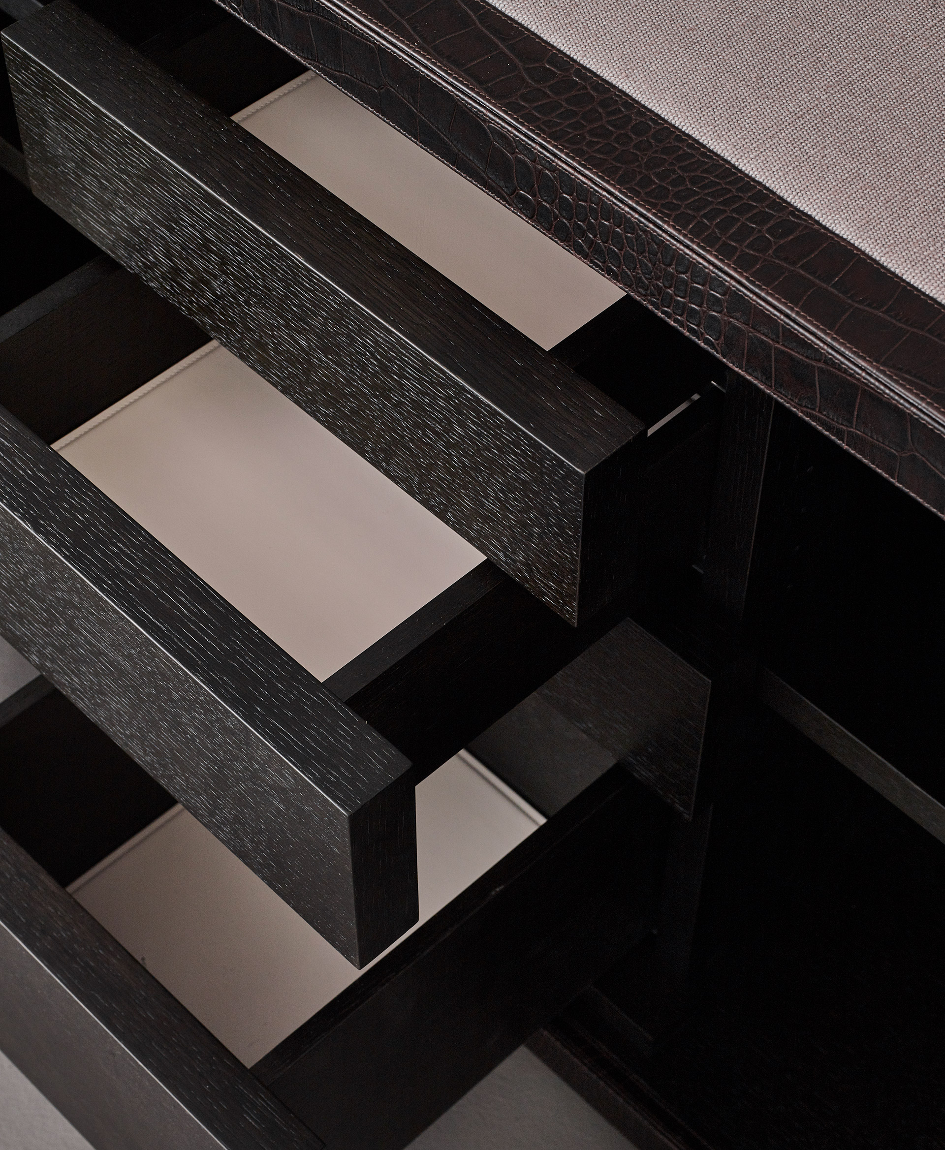 Drawers' detail of Future Voyager Atto II, a wooden cabinet covered in leather and fabric with handles and placemats in leather from Promemoria's catalogue | Promemoria
