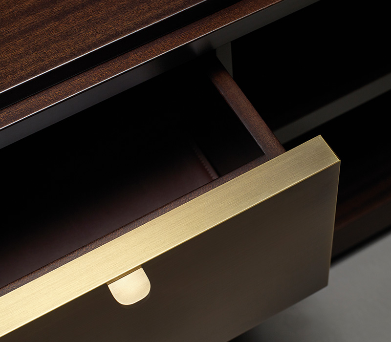 Bronze drawers' detail of Nightwood, a wooden low cabinet with drawers with bronze details and leather placemats from Promemoria's Amaranthine Tales collection | Promemoria
