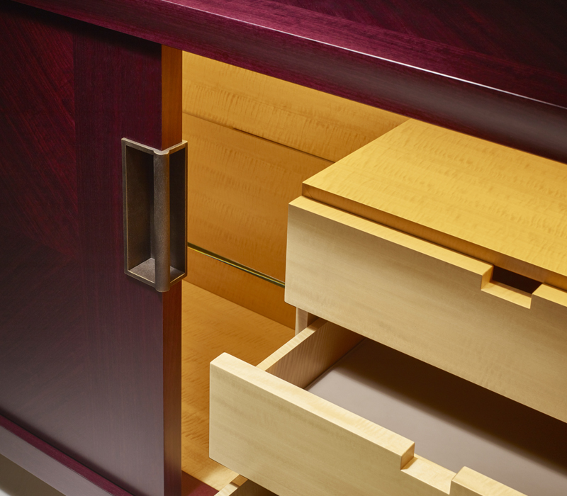 Drawers' detail of Oolong, a low wooden cabinet with sliding doors with leather shelves and drawers fronts and bronze handles from Promemoria's catalogue | Promemoria