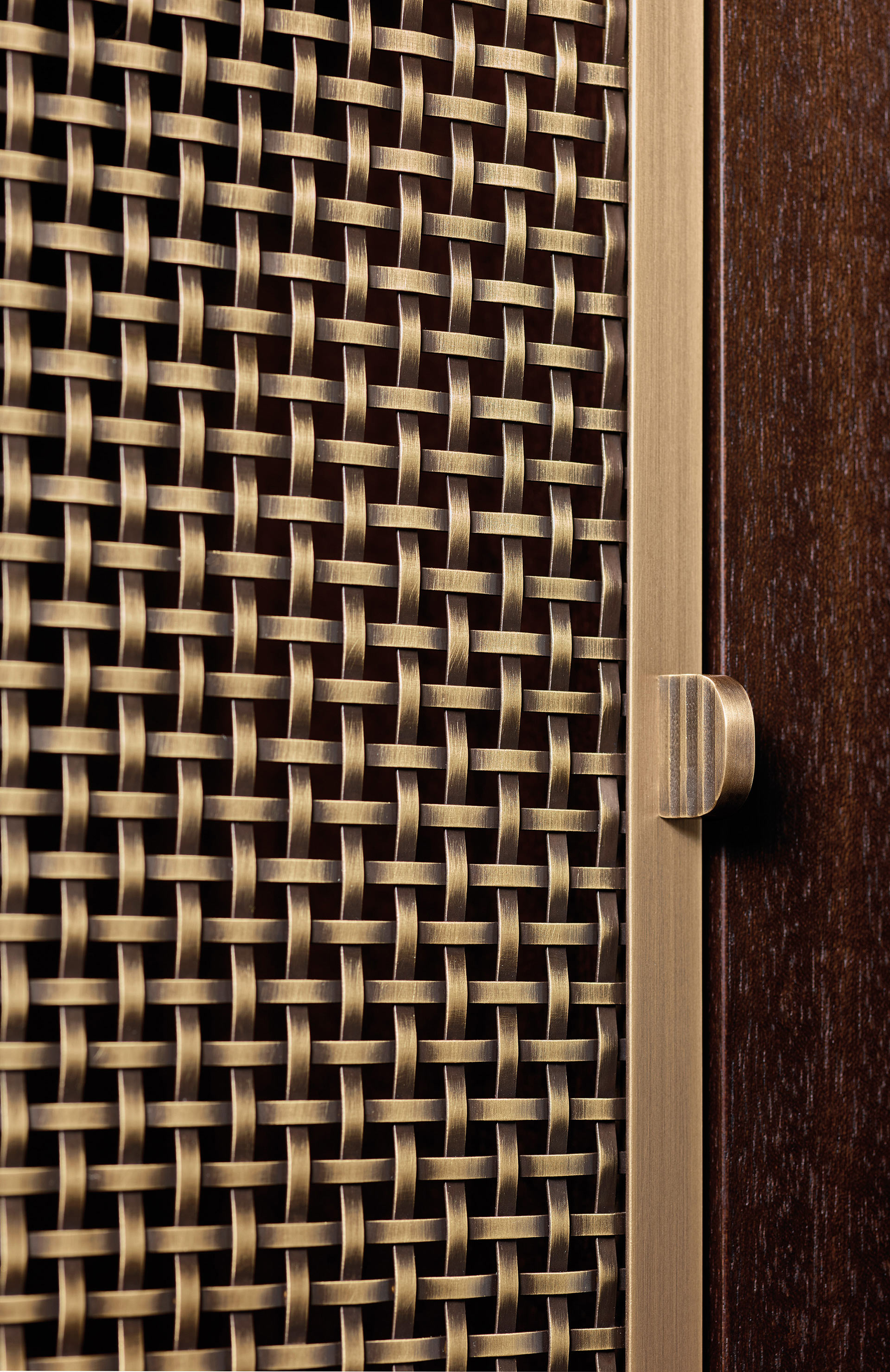 Detail of the bronze handle of Nightwood, a wooden modular bookcase with bronze details, from Promemoria's Night Tales collection | Promemoria