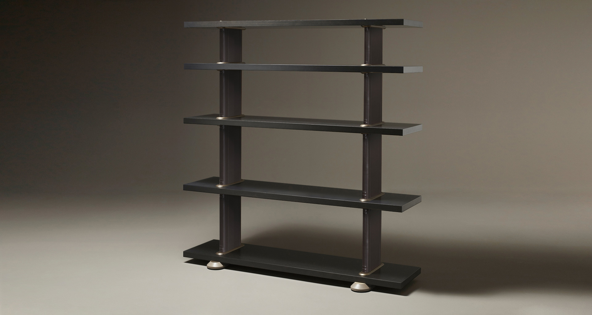 Peggy is a modular wooden bookcase with cloth or leather covered supports and bronze details, from Promemoria's catalogue | Promemoria