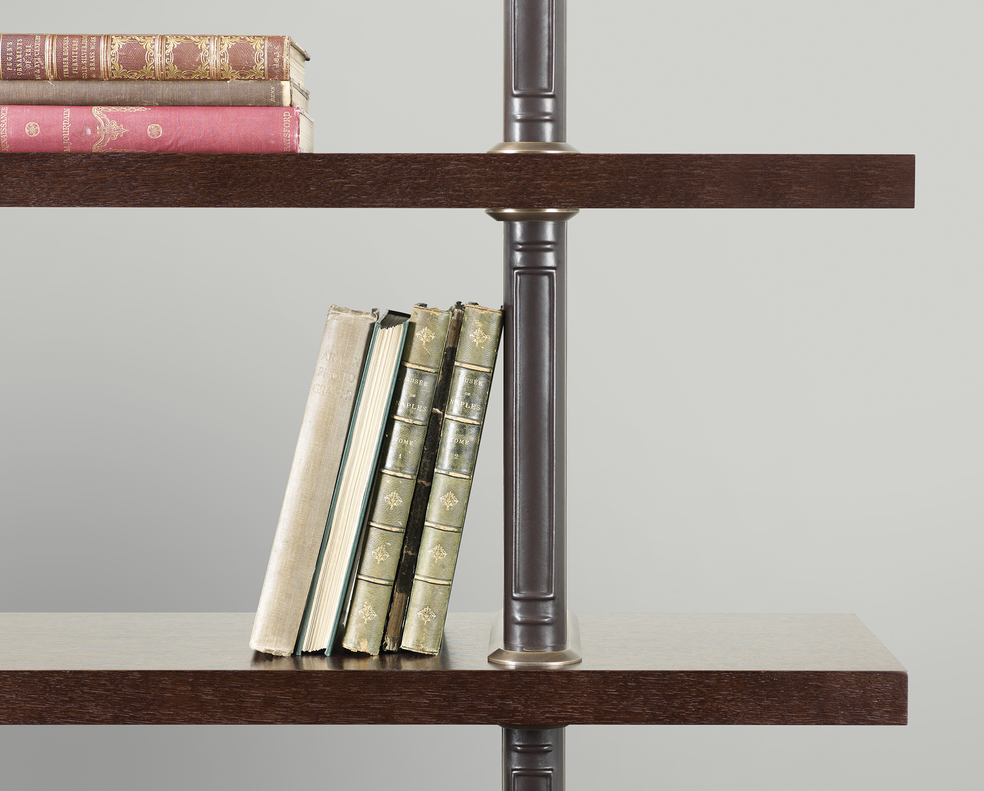 Detail of Peggy, a modular wooden bookcase with cloth or leather covered supports and bronze details, from Promemoria's catalogue | Promemoria