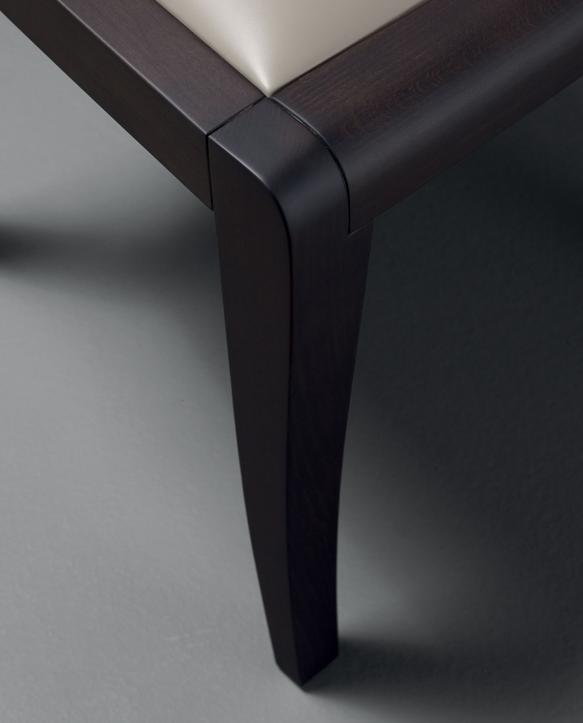 Armrest detail of Eloise, a wooden dining chair with leather seat, available with or without armrests and high or low-backed, from Promemoria's catalogue | Promemoria