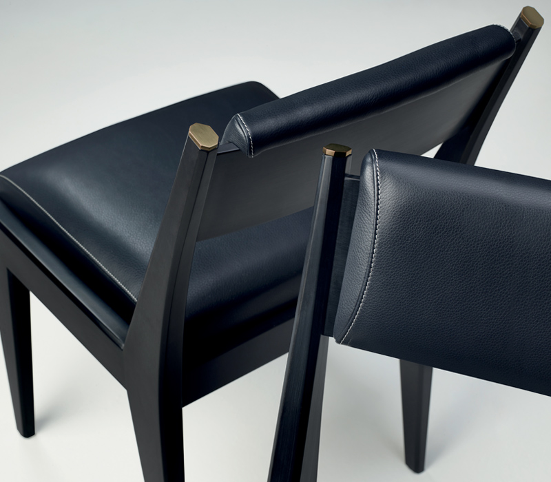 Iris is a wooden chair with bronze details and leather cushions, from Promemoria's Indigo Tales | Promemoria