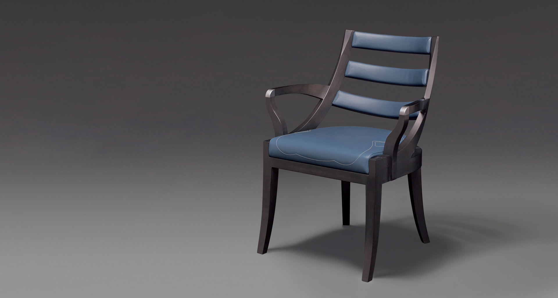 Judith is a wooden dining chair with a bronze detail on the armrest, from Promemoria's catalogue | Promemoria