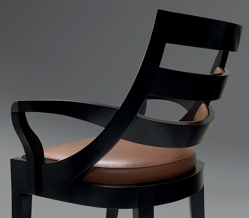 Back detail of Judith, a wooden dining chair with a bronze detail on the armrest, from Promemoria's catalogue | Promemoria