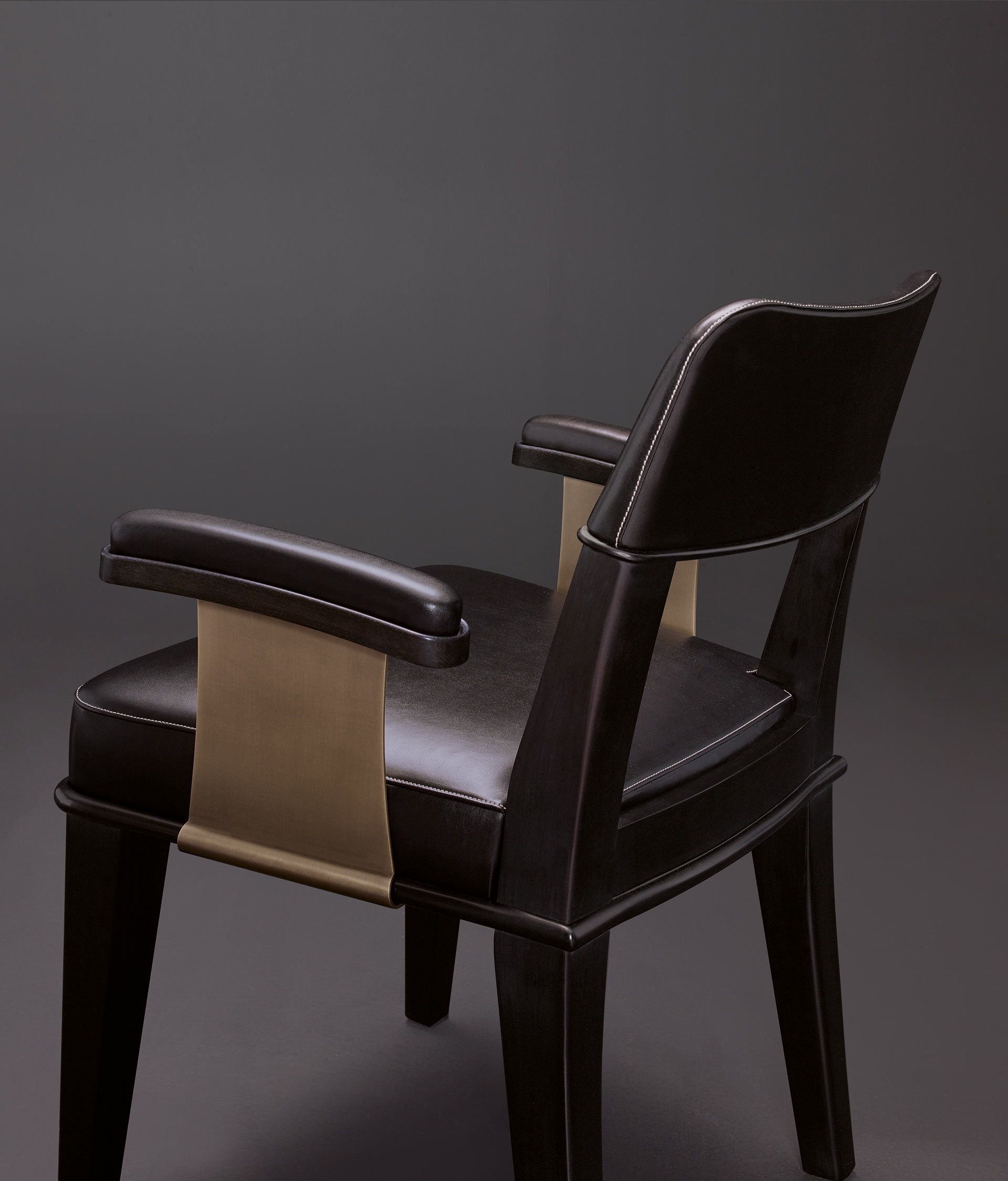 Detail of Vespertine, a wooden dining chair with leather seat and back and with armrests with bronze details, from Promemoria's Night Tales collection | Promemoria