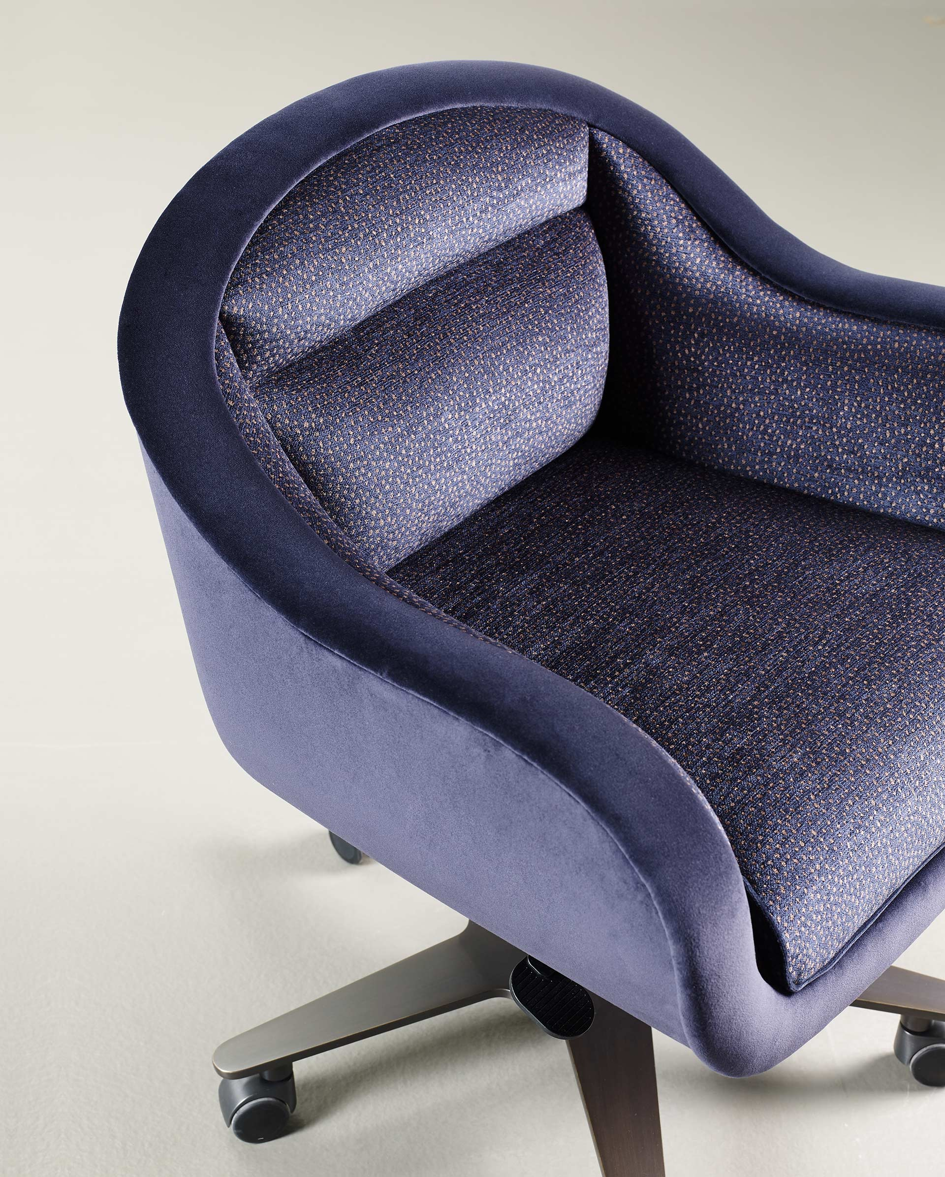 Vittoria is an office chair with a metal or bronze base, covered in fabric or leather with a bronze handle on the back, from Promemoria's catalogue | Promemoria