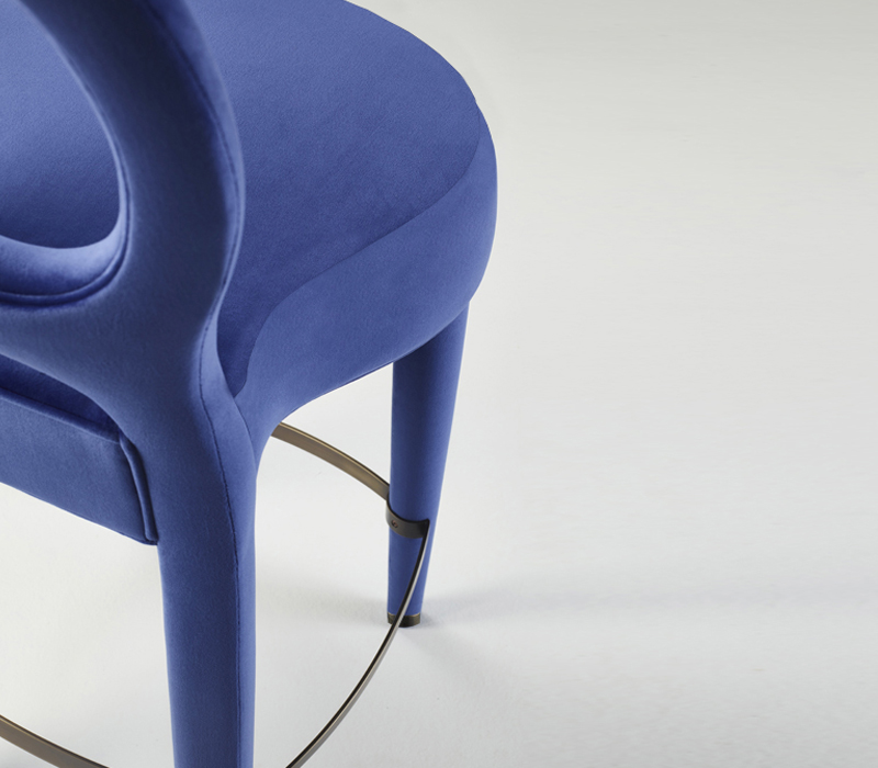 Detail of Bilou Bilou, a wooden stool with fabric or leather seat and bronze footrest and with the same aesthetic of the Bilou Bilou chair, from Promemoria's catalogue | Promemoria
