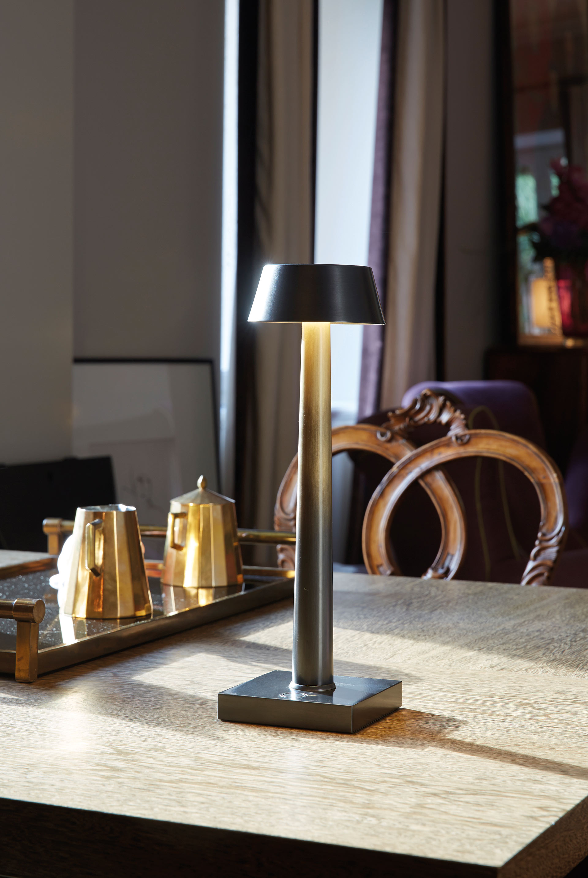 Fiammetta is a portable table LED lamp with bronze structure and touch switch, from Promemoria's catalogue | Promemoria