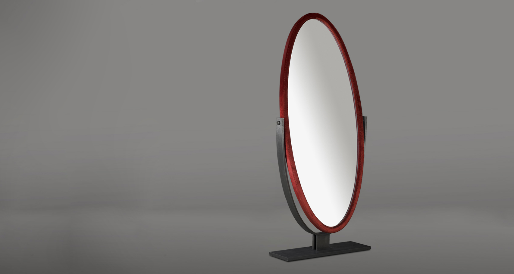 Ingrid is an elliptical revolving mirror with a bronzed metal base, from the Promemoria's catalogue | Promemoria