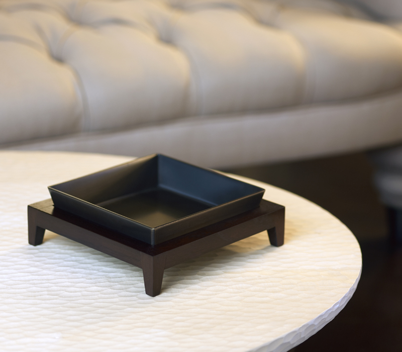 Detail of Santos, a wooden tray with a bronze base, from Promemoria's catalogue | Promemoria