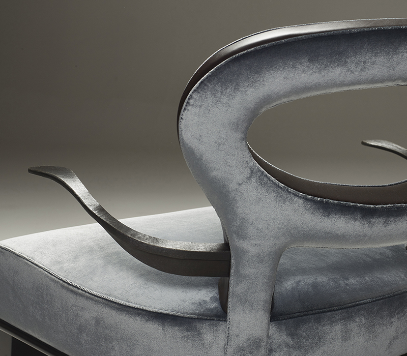 Bronze arms detail of Roka Large, a large wooden armchair covered in fabric and leather, from Promemoria's catalogue | Promemoria