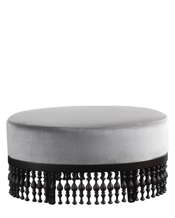Istanbul is a fabric or leather pouf with a wooden fringed base, from Promemoria's Capsule Collection by Bruno Moinard | Promemoria
