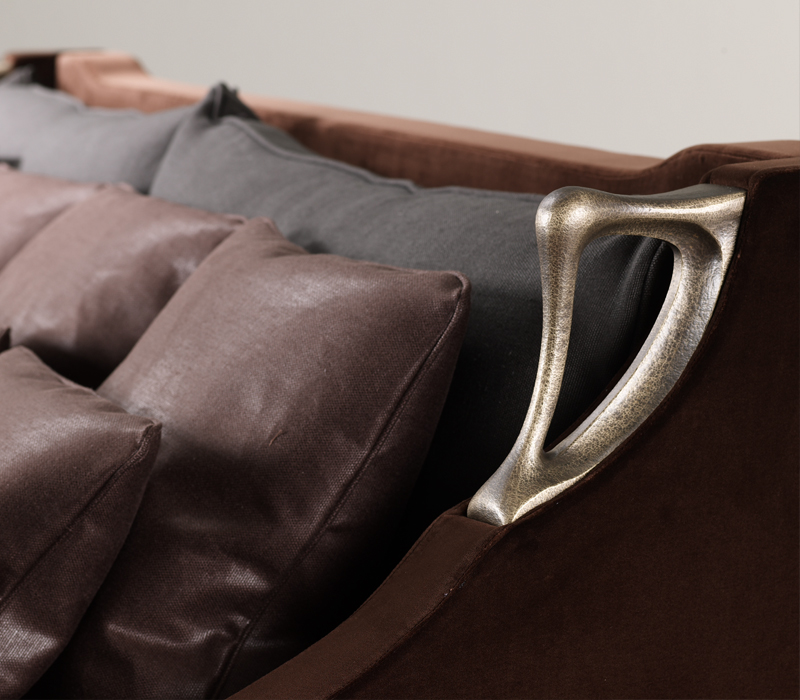 Bronze side handles detail of Albert, a wooden sofa covered in fabric, from Promemoria's catalogue | Promemoria