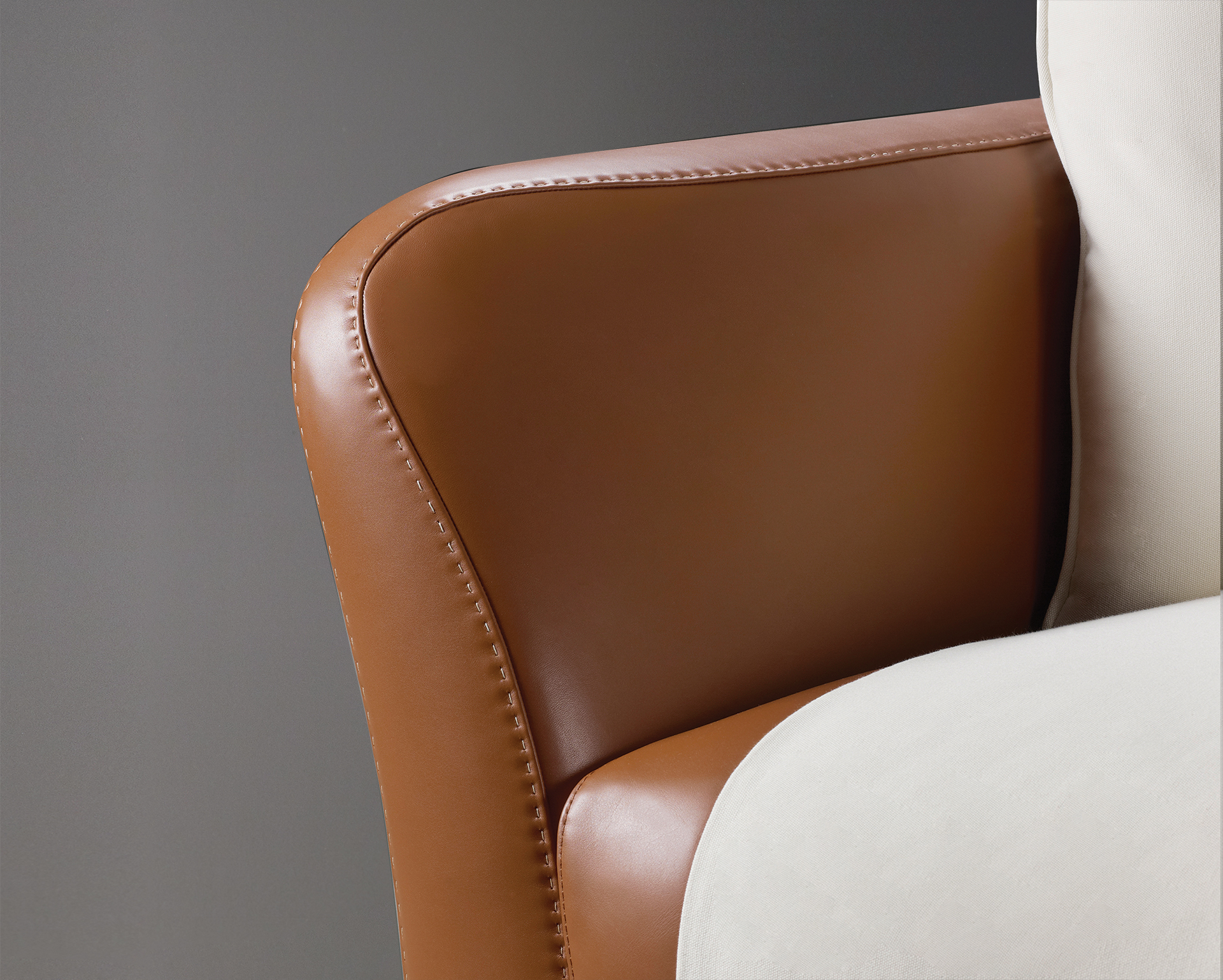 Leather detail of Shangri-la, a wooden sofa covered in leather and fabric, from Promemoria's catalogue | Promemoria