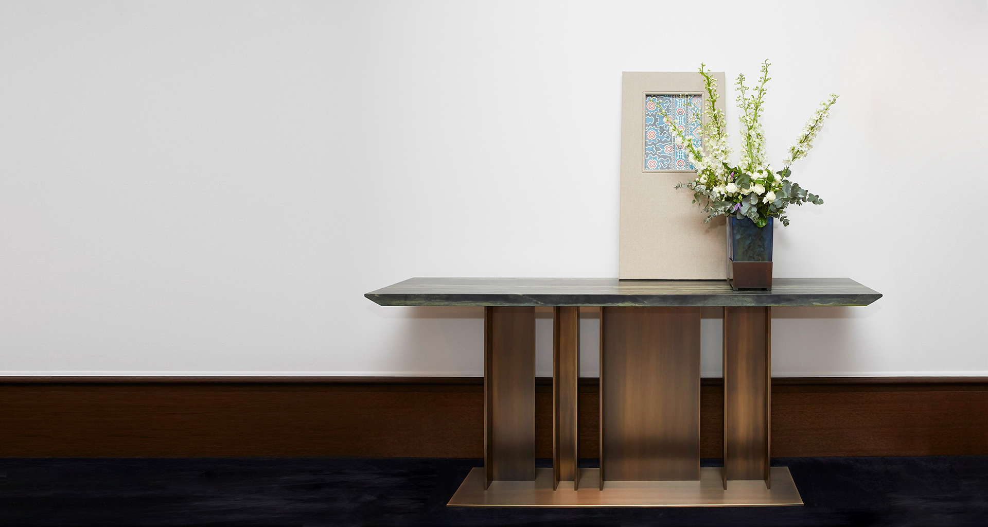 Nila is a console with bronze base and wooden top, from Promemoria's Indigo Tales collection | Promemoria