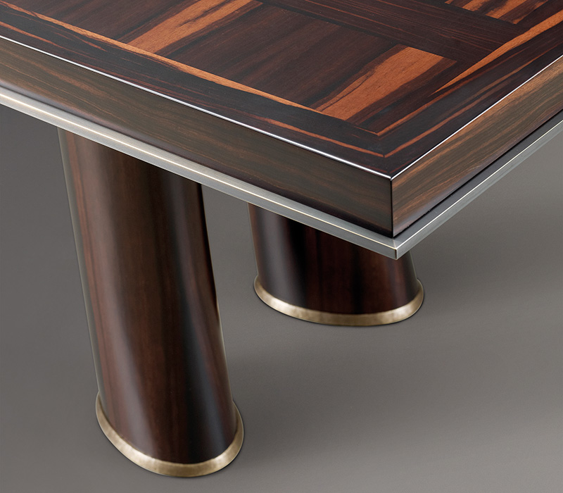 Bronze profile detail of Andalù, a wooden dining table with bronze feet, from Promemoria's catalogue | Promemoria