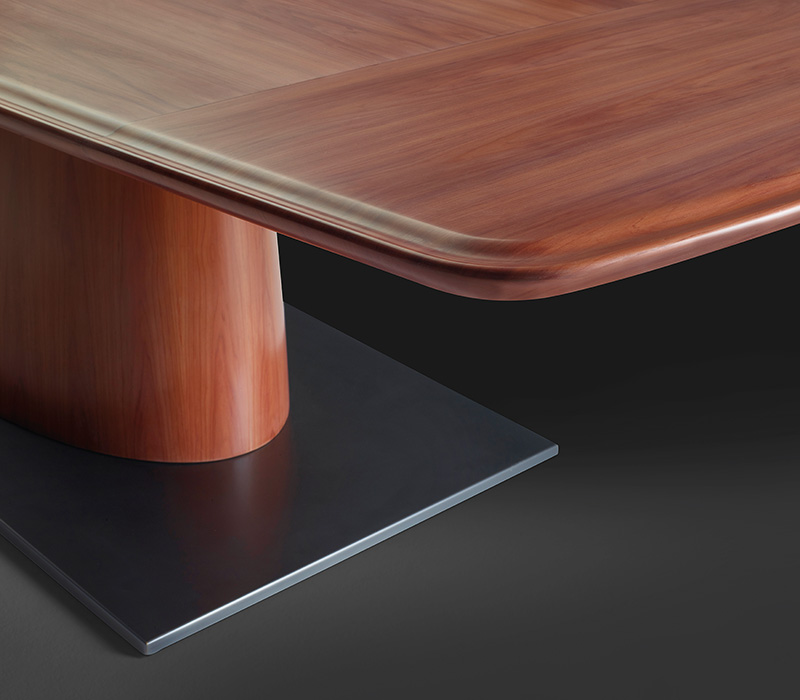 Bronze base detail of Gerardo, a wooden dining table with rounded and fluted profiles, from Promemoria's Indigo Tales collection | Promemoria